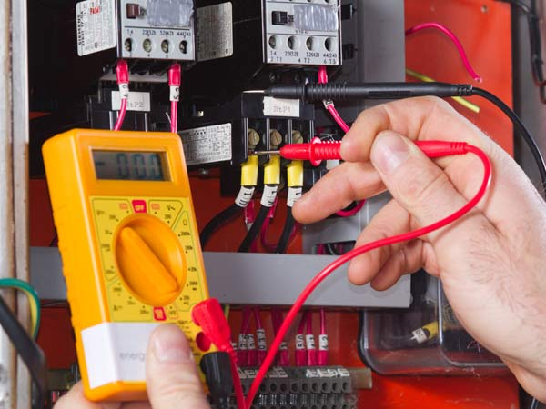 electrician testing electrical panel with voltmeter